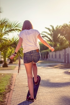 Back view of beautiful young girl with short shorts riding in a skateboard outdoors on  summer. warm tones edition.