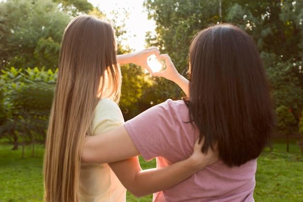 Лучшие друзья вид сзади, делая сердце на солнечном свете