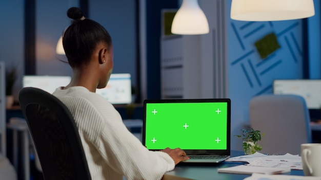 Back view of black business woman looking at laptop with greenscreen, green mockup, chroma key desktop sitting at desk in start up business office overworking
