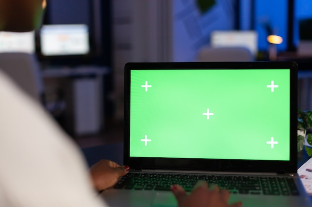 Back view of black business woman using laptop with green screen, green mockup, chroma key desktop sitting at desk in start up business office overworking