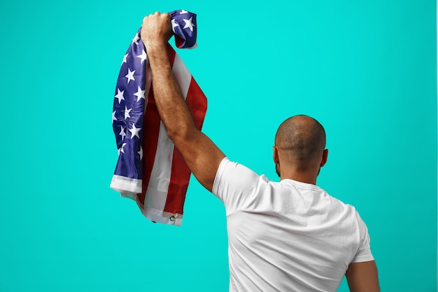 Back view of a black man holding usa flag on turquoise