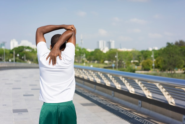 Back view of black man warming up in open air.