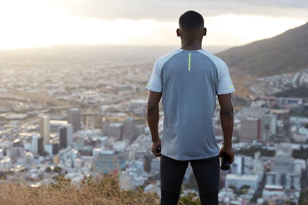 Back view of black sporty man wears casual t shirt, holds bottle with fresh drink, looks from above at city buildings, admires mountain landscape, enjoys speed and outdoor workout. sport concept