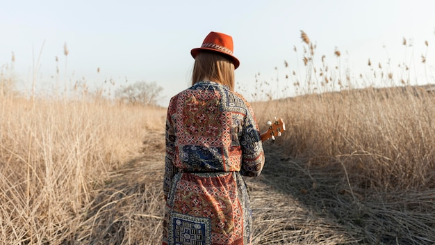 Back view of bohemian woman with ukulele in nature