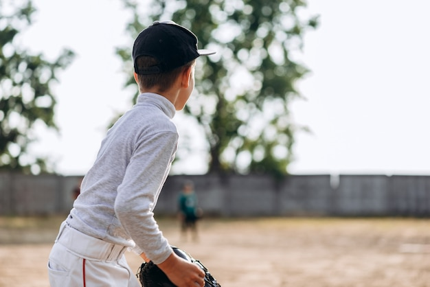 Back view of a boy baseball player playing baseball