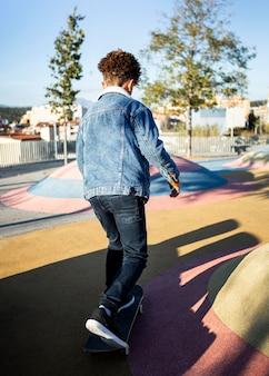 Вид сзади мальчик катается на скейтборде в парке