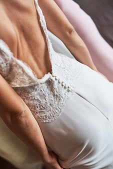 Back view of a bride in an elegant white wedding dress with a open back.