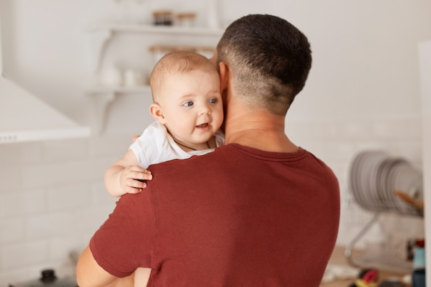 Back view of brunette father wearing burgundy t shirt with charming infant daughter, man hugging his baby girl with great love, posing in light room with kitchen set on background.