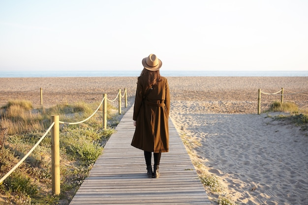 Back view of brunette girl in hat and coat standing on boardwalk by seaside
