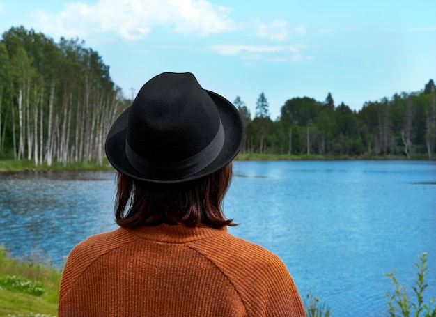 Back view of brunette lady looking at lake in karelia