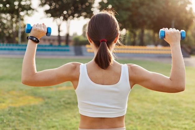 Vista posteriore di una donna bruna con capelli scuri e coda di cavallo che tiene manubri e fa esercizi allo stadio, allenando bicipiti e tricipiti, attività all'aperto.