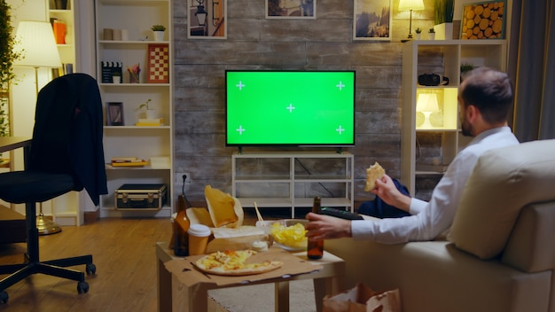 Vista posteriore dell'uomo d'affari che si gode la sua pizza mentre guarda una tv con schermo verde mock up