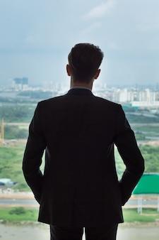 Vista posteriore di uomo d'affari in piedi dalla finestra