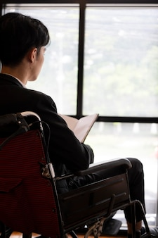 Back view of businessman in wheelchair sitting in office and look through window.