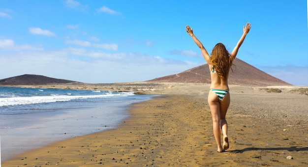 Back view carefree beautiful bikini woman with raised arms walking on the beach on summer day. panoramic banner template web. copy space.