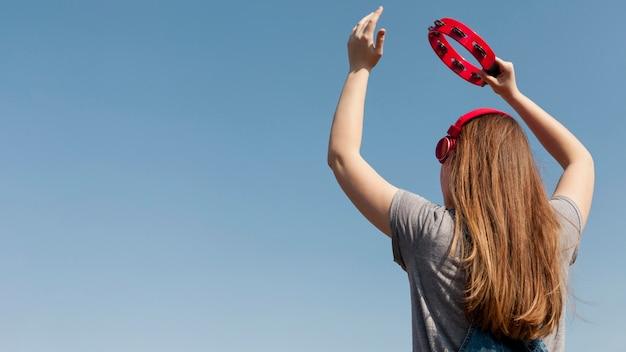 Punto di vista posteriore della donna spensierata con le cuffie che tengono tamburello