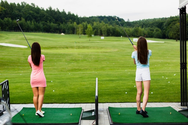 Back view of casual girls at a golf field