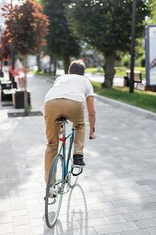 Вид сзади случайные мужчины езда на велосипеде на открытом воздухе