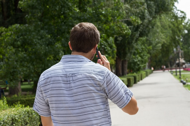 Back view of casual man walking in park and having phone conversation.