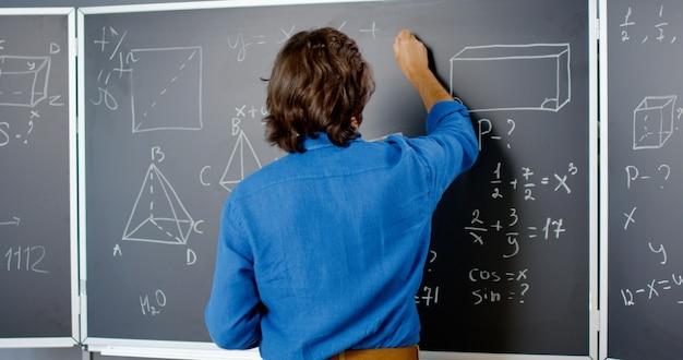 Вид сзади кавказский мужской преподаватель написание формул математики или физики мелом на доске. учитель человек работает в школе. урок математики. математик. уравнение геометрии или алгебры. задний.