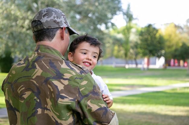 Vista posteriore dell'uomo caucasico che tiene il bambino e indossa l'uniforme dell'esercito. ragazzino allegro che si siede sulle mani del padre, abbracciando il papà e sorridendo felicemente. ricongiungimento familiare, paternità e concetto di ritorno a casa