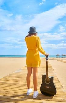 Vista posteriore di un adolescente caucasico con la chitarra in spiaggia