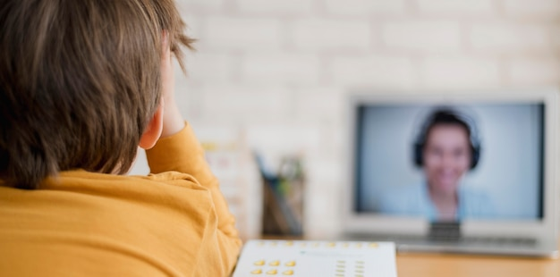 Back view of child being tutored at home through online class