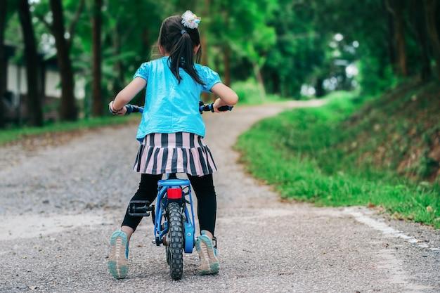 夕日の光の運動で夜の村の公園でサイクリングの背面の子女の子。