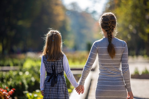 Back view of child girl and mother in dresses together holding hands on warm day outdoors on sunny.