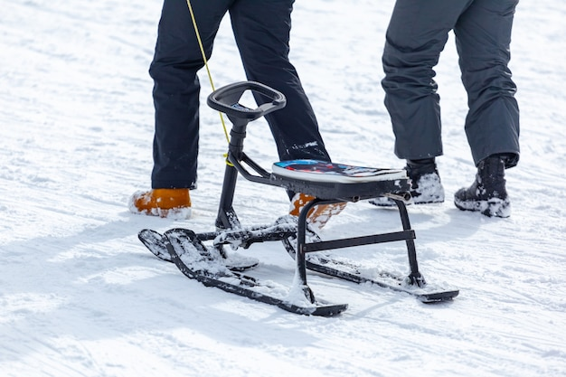 Back view of child in pulling sledge and running up snowy slope while spending time on ski resort