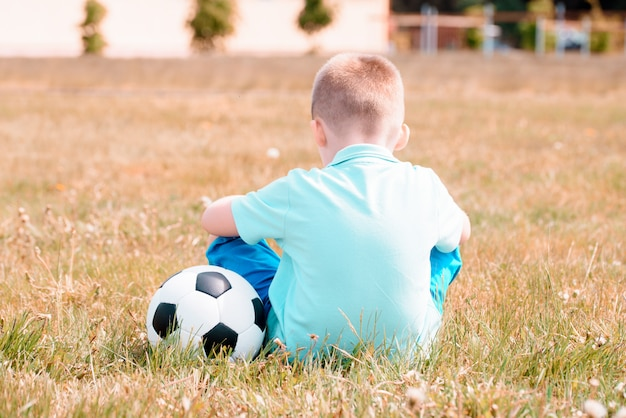 Back view of a child in sportswear with soccer ball.