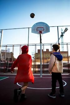 屋外で一緒にバスケットボールをしている子供たちの背面図