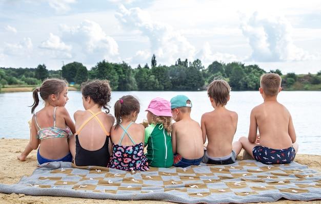Вид сзади дети сидят у реки и отдыхают после купания, загорают, едят мороженое.