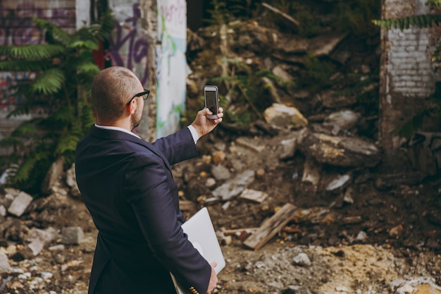 Back view close up cropped businessman in white shirt, classic suit, glasses. man doing selfie on phone near ruins debris, stone building outdoors. mobile office concept. copy space for advertisement.