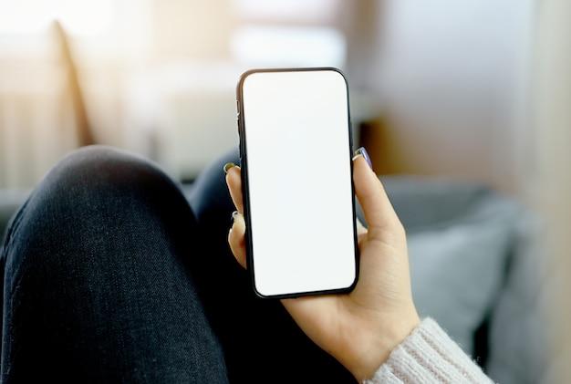 自宅のベッドに座っている白い空白の空の画面でスマートフォンを持って使用している女性の手の背面図のクローズアップ。