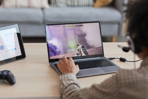 ラップトップ、コピースペースを介してオンラインでビデオゲームをプレイしているアフリカ系アメリカ人の少年の背面図のクローズアップ