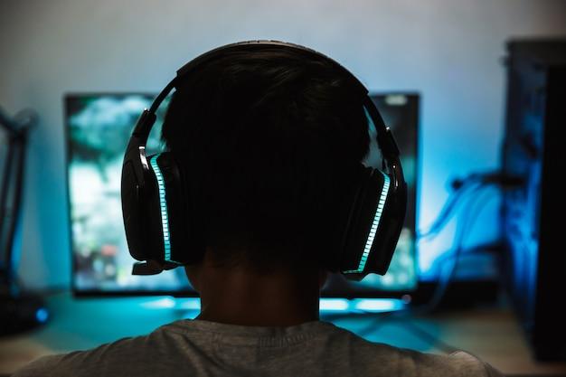 Вид сзади крупным планом молодого мальчика-геймера, играющего в онлайн-игры на компьютере в темной комнате, в наушниках с микрофоном