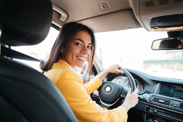 Back view of a confident smiling woman driving car