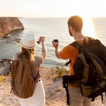日没時にコーヒーを楽しんでいる背面図のカップル
