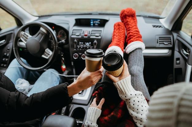 車の中で一緒にコーヒーを楽しんでいる背面図のカップル