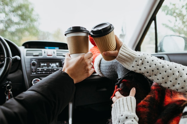 Back view couple enjoying a cup of coffee together in the car