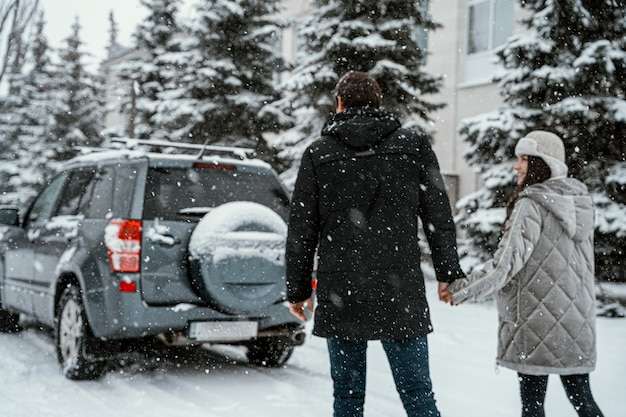 Back view of couple enjoying the snow while on a road trip with car