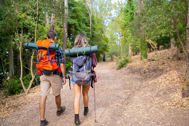Back view of couple going along road in forest. long-haired woman and man carrying backpacks and hiking on nature together. green trees on background. tourism, adventure and summer vacation concept