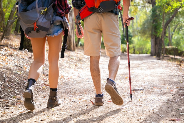 Back view of couple hiking together on road. unrecognizable man and woman walking on nature. legs of tourists trekking with backpacks in sunny day. tourism, adventure and summer vacation concept