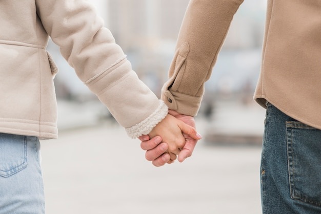 Back view of couple holding hands outside