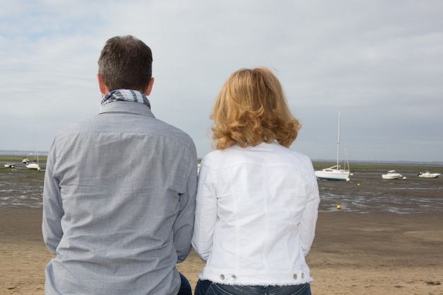 Back view of a couple in holidays or vacation near sea side or beach