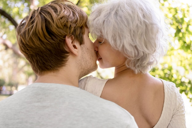 Back view of couple kissing in nature