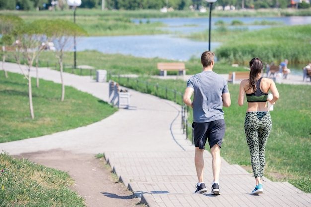 Back view of couple running outdoors