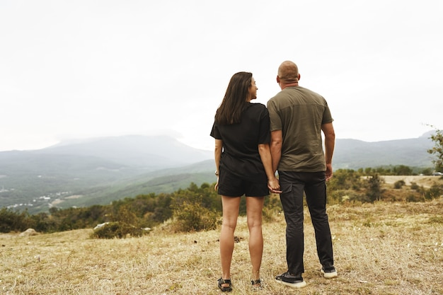 Back view of couple standing and looking at foggy mountains