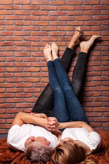 壁に足で滞在背面カップル